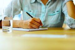 Escrita fêmea da mão em um papel Fotos de Stock