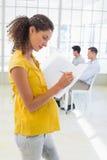 Escrita grávida ocasional da mulher de negócios no dobrador Imagens de Stock