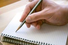 Escrita humana algo no caderno do papel pessoal imagens de stock royalty free