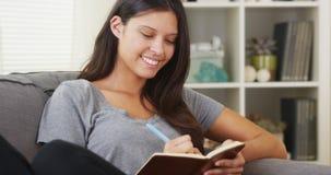 Escrita latino-americano ocasional da mulher em seu jornal imagens de stock royalty free