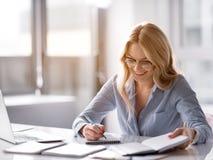 Escrita loura alegre da mulher no caderno no local de trabalho imagem de stock