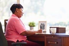 Escrita madura da mulher no caderno que senta-se na mesa imagem de stock