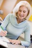Escrita madura do estudante fêmea na classe Imagem de Stock Royalty Free