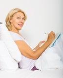 Escrita madura loura da mulher no diário Fotografia de Stock Royalty Free