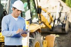 Escrita masculina do arquiteto na prancheta contra o escavador no canteiro de obras Imagem de Stock