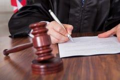 Escrita masculina do juiz no papel Fotografia de Stock