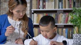Escrita nova asiática da mãe com filho, mulheres que ajudam a criança, sentando-se atrás da tabela, criança asiática que faz trab vídeos de arquivo