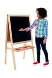 Escrita nova da menina da escola no quadro-negro Imagens de Stock