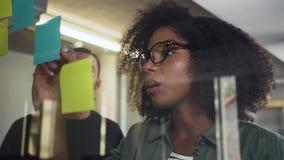 Escrita nova da mulher de negócios na nota adesiva sobre o vidro com seu colega filme