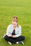 Escrita nova da mulher do moderno em seu caderno no parque Imagens de Stock