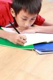 Escrita nova do menino algo no livro foto de stock