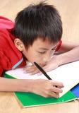 Escrita nova do menino algo no livro imagem de stock royalty free