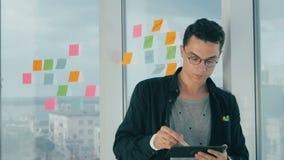 Escrita nova ocasional da sessão de reflexão do homem de negócios em notas pegajosas na janela no escritório filme