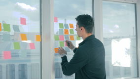 Escrita nova ocasional da sessão de reflexão do homem de negócios em notas pegajosas na janela no escritório vídeos de arquivo