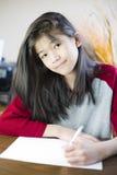 Escrita ou desenho da menina dos anos de idade dez no papel Imagens de Stock