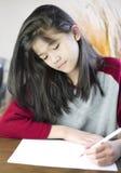 Escrita ou desenho da menina dos anos de idade dez no papel Fotografia de Stock Royalty Free