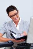 Escrita séria da mulher de negócio em sua agenda Imagens de Stock
