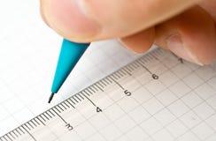 Escrita Uma mão escreve em uma folha de papel com um lápis Fotos de Stock Royalty Free