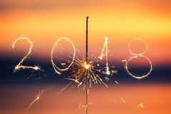 2018 escrito com o fogo de artifício da faísca no fundo do por do sol, n feliz fotografia de stock