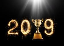 2019 escrito com o fogo de artifício da faísca com o troféu dourado o do campeão fotos de stock