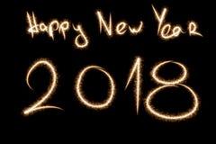2018 escrito con el fuego artificial de la chispa en fondo negro, ne feliz Foto de archivo