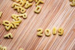 2019 escrito con las pastas del alfabeto en el fondo de madera fotos de archivo libres de regalías
