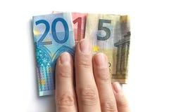 2015 escrito con los billetes de banco de los euros en una mano Imagen de archivo libre de regalías