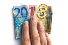 2018 escrito con los billetes de banco de los euros en una mano aislada en el fondo blanco Imagenes de archivo