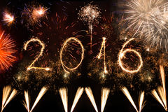2016 escrito con los fuegos artificiales como fondo Foto de archivo