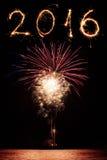 2016 escrito con los fuegos artificiales como fondo Foto de archivo libre de regalías