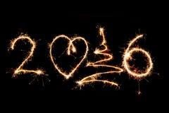 2016 escrito con los fuegos artificiales como fondo Imagen de archivo libre de regalías