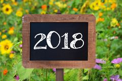 2018 escrito em um sinal de madeira, em uns girassóis e em umas flores selvagens Imagem de Stock Royalty Free