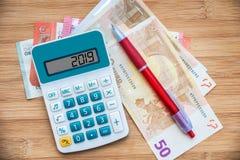 2019 escrito em uma calculadora e em cédulas dos euro no fundo de madeira fotografia de stock royalty free