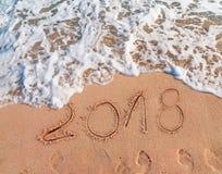2018 escrito en Año Nuevo de la playa arenosa está viniendo como día de fiesta de la fecha Imagenes de archivo