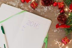 2016 escrito en el cuaderno con las decoraciones de la Navidad Imagen de archivo libre de regalías