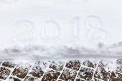 2018 escrito en la nieve blanca la nieve miente en la teja de la acera Fotografía de archivo