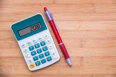 2018 escrito en una calculadora y una pluma en el fondo de madera imagen de archivo libre de regalías