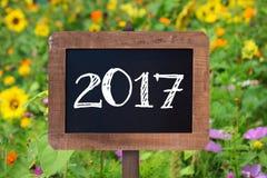 2017 escrito en una muestra de madera, girasoles y flores salvajes Fotografía de archivo libre de regalías