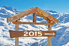 2015 escrito en una señal de dirección de madera, paisaje de la montaña de la nieve Fotografía de archivo libre de regalías
