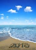 2018 escrito no Sandy Beach com água da onda do mar fotografia de stock royalty free