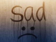 Escrito por triste e por Emoji no vidro misted r foto de stock royalty free