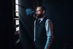 Escritor barbudo en los vidrios que fuman un cigarrillo foto de archivo