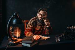 Escritor barbudo en los vidrios que fuman un tubo imagen de archivo libre de regalías