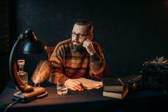 Escritor barbudo en los vidrios que se sientan en la tabla fotografía de archivo libre de regalías