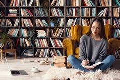 Escritor da jovem mulher em notas de assento da escrita da ocupação criativa da biblioteca em casa fotos de stock