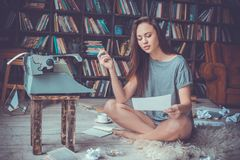 Escritor de la mujer joven en la lectura que fuma del empleo creativo de la biblioteca en casa imagen de archivo libre de regalías