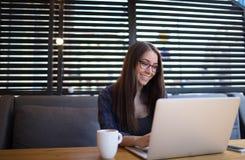 Escritor feliz do conteúdo web da mulher que trabalha no laptop na cafetaria imagem de stock