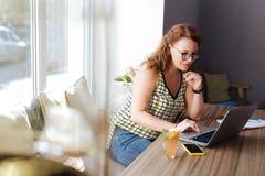 Escritor free lance pelirrojo que se sienta en café mientras que trabaja difícilmente Foto de archivo libre de regalías