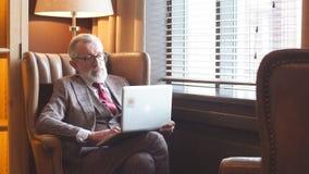 Escritor masculino idoso elegante que veste a roupa elegante que trabalha no portátil vídeos de arquivo