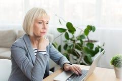 Escritor mayor de la mujer en el funcionamiento blanco en el nuevo artículo fotos de archivo libres de regalías